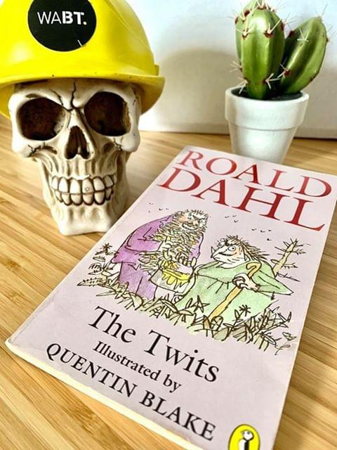 We Are Brass Tacks. Internal comms agency. Fred the Head. Book of the month. The Twits. Skull waering yellow hard hat on desk sat beside pink book and tiny cactus
