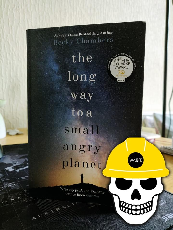 We Are Brass Tacks. Internal comms agency. Fred the Head. Book of the month. The Long Way to a Small Angry Planet. Vector graphic of skull wearing yellow hard hat overlayed on navy covered book.
