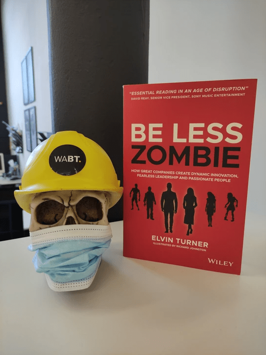 We Are Brass Tacks. Internal comms agency. Fred the Head. Book of the month. Be Less Zombie. Red book standing beside skull with hard hat and face mask.