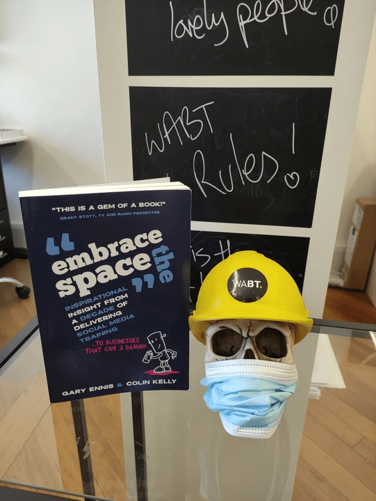 We Are Brass Tacks. Internal comms agency. Fred the Head. Book of the month. Skull with hard hat sitting on a glass table next to a blue book.