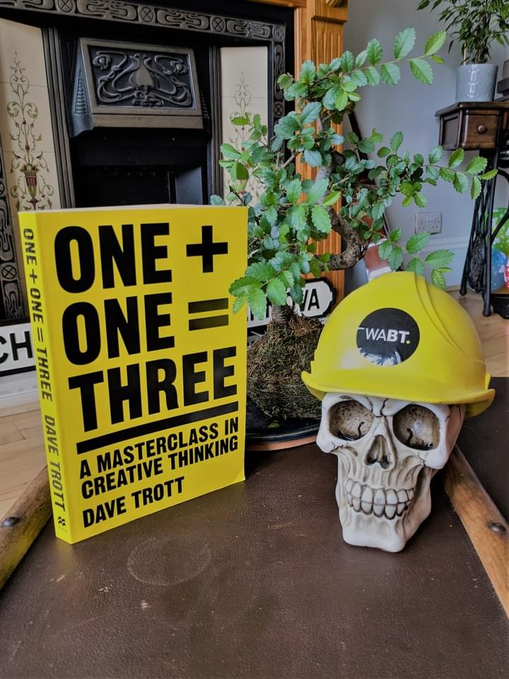 We Are Brass Tacks. Internal comms agency. Fred the Head. Book of the month. One Plus One equals Three. Skull with hard hat sitting on brown trunk next to yellow book.