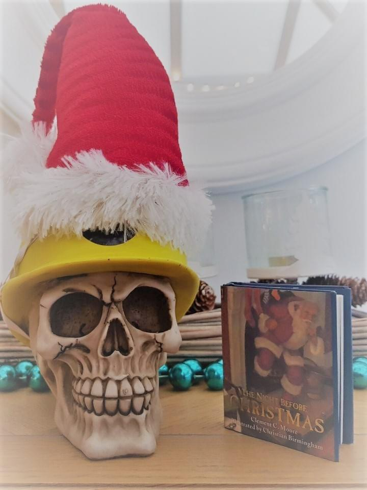We Are Brass Tacks. Internal comms agency. Fred the Head. Book of the month. The night before Christmas. Skull wearing yellow helmet and Santa hat sitting beside book standing up.