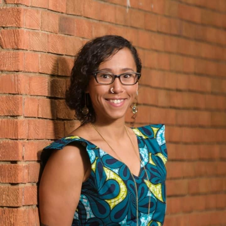 aidx Research Advisor Dacia Douhaibi standing in front of a brick wall in Nairobi, Kenya