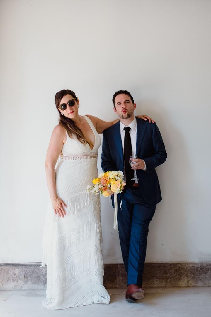 A cool groom holds his bride's bouquet with locally-grown yellow ranunculus and roses, while she strikes a pose in a stunning fringed wedding dress and chic sunglasses.