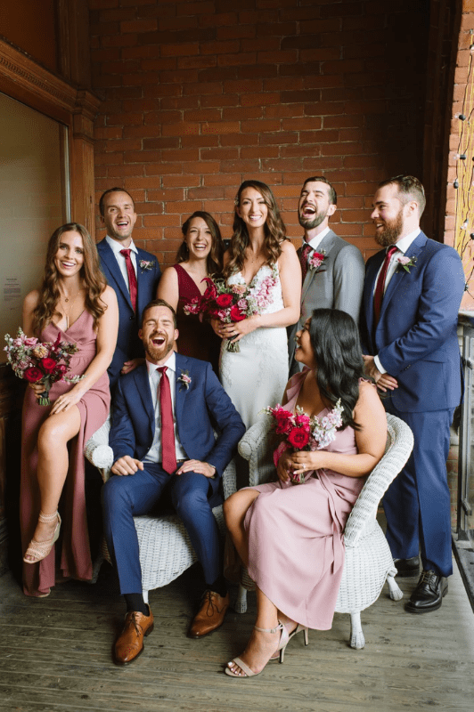A group photo of a wedding party in Toronto, dressed in navy and dusty rose with burgundy and mauve flowers