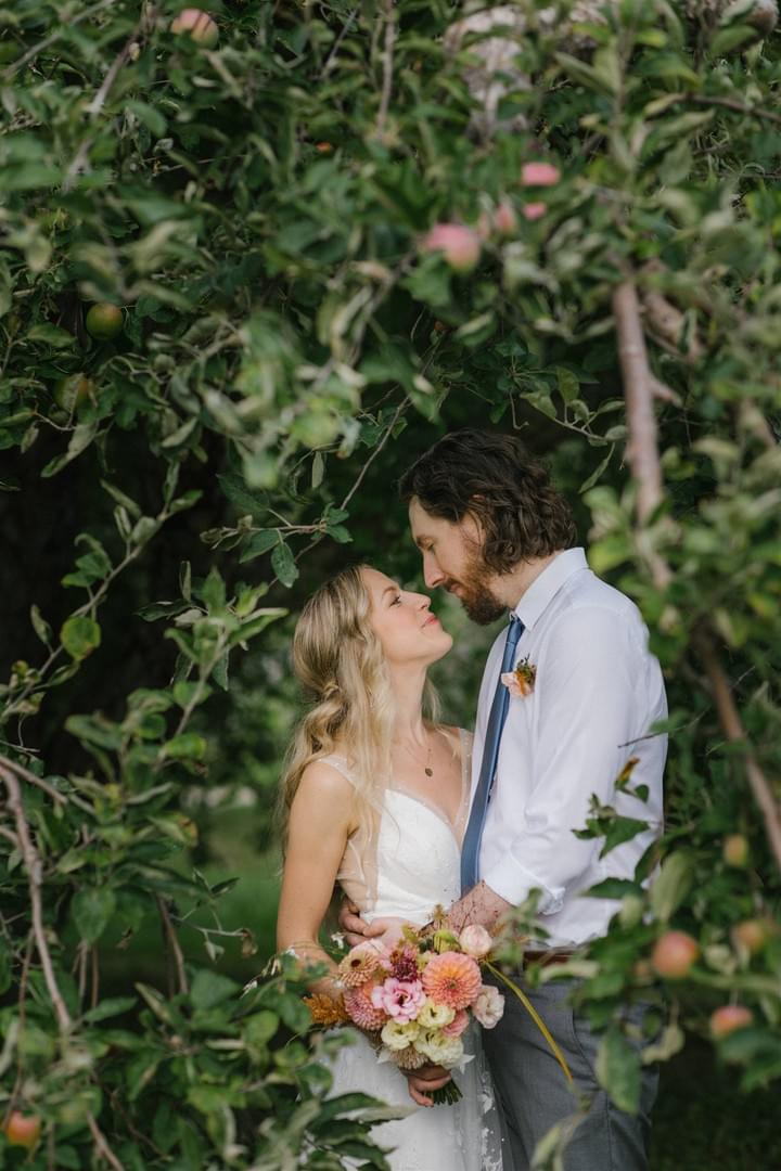 Bride and groom embrace in an apple orchard. Bridal bouquet with locally-grown dahlias, zinnias, and lisianthus in peach and pink.