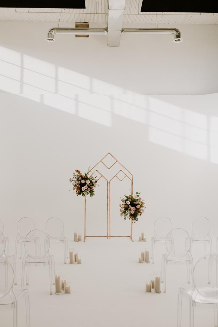 Cathedral-style copper arbor decorated with lush floral swags in blush and burgundy florals for a minimalist ceremony setup at District 28 events.