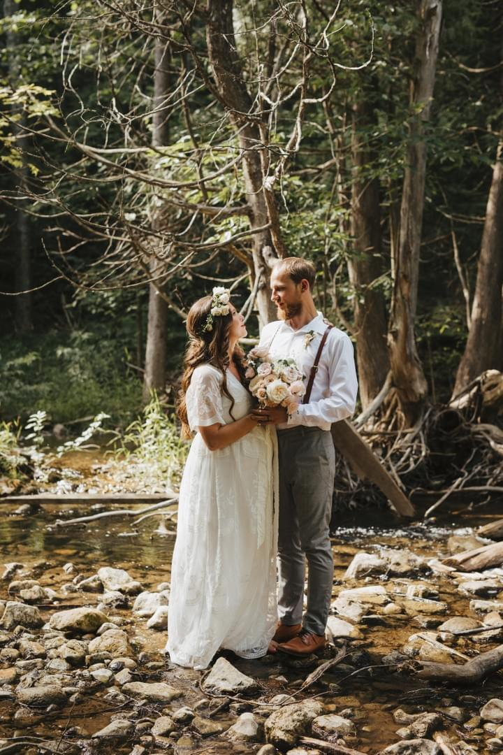 Pregnant bride in beautiful boho dress with white and blush bridal bouquet and flower crown