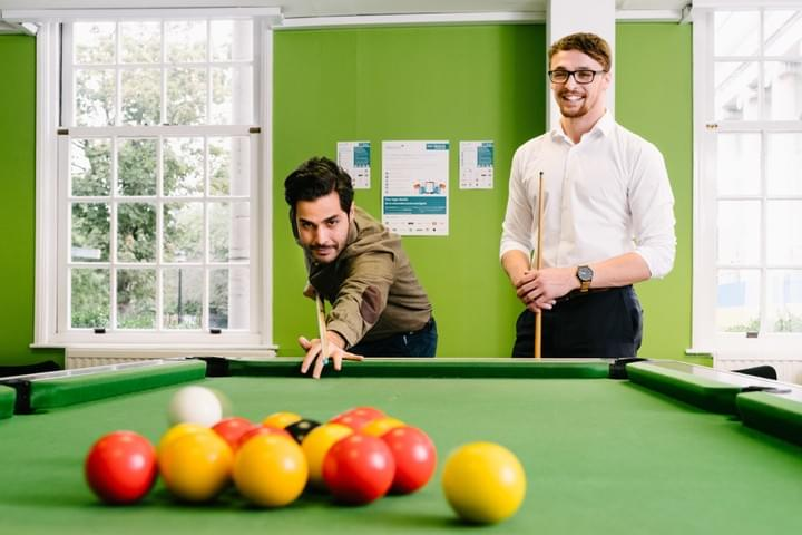 Wescot Employees playing pool in Bolton office.