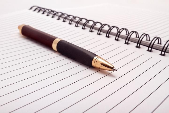 A pen lying on an open empty page of a notebook