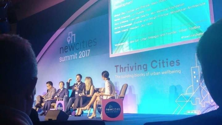 Julia Suh is sitting with four others on stage at New Cities Summit
