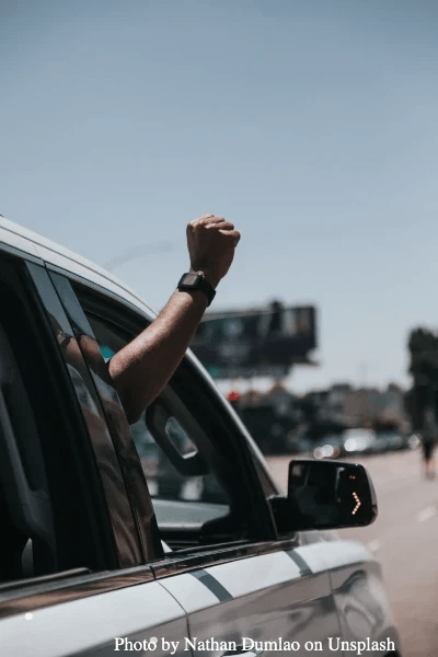 Photo of man's arm raising fist in solidarity out of car window