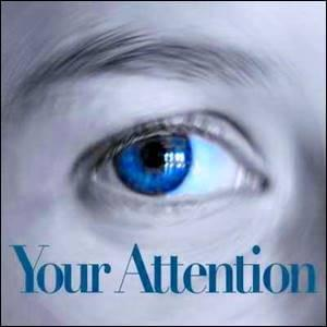 The right eye of a person with the words Your Attention below it
