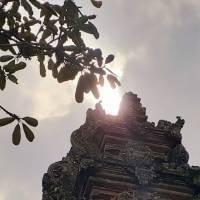 Some kind of temple, photographed from the ground looking up, partly covering the sun