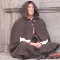 A man wearing a brown cloak, sitting on the ground like a beggar