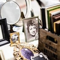 A collection of old things - a black and white photograph, a brooch, a mirror, a magnifying glass and several books
