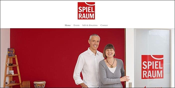 smiling silver haired caucasian man Michael Hallinger in white long sleeved shirt standing behind smiling caucasian woman Dagmar Thürnagel wering grey sweater and archetypal lineage talisman on deep red background, Spiel Raum Planegg