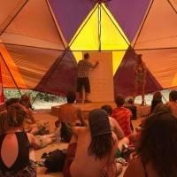 A man and a woman delivering a work talk inside a huge tent, a group of people are sitting on the ground and listening to them