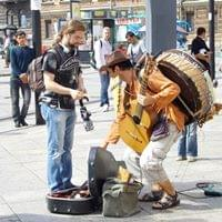Aman giving money to a busker with a guitar and a drum