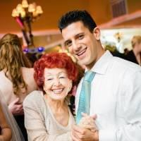 An older lady and a young man dancing together at an indoors celebration, grinning at the camera.