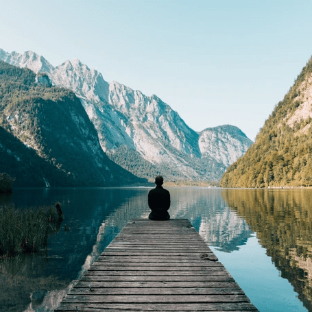Man sitting on a dock looking at a mountain