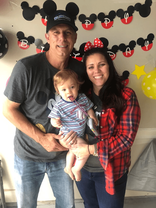 Family photo of parents with baby Mickey Mouse theme.