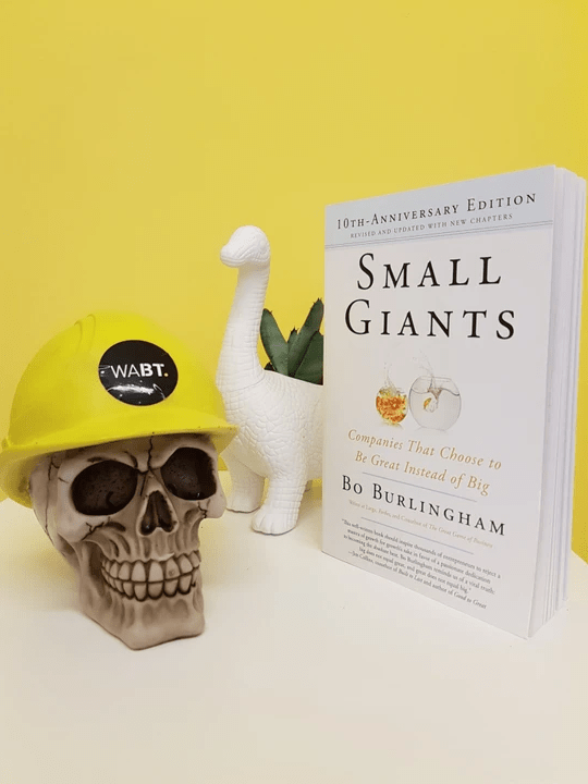We Are Brass Tacks. Internal comms agency. Fred the Head. Book of the month. SKull wearing hard hat next to white dinosaur plant pot and book.