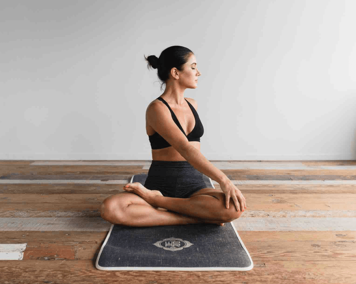 Woman sits on a yoga mat, doing a twist in a cross legged pose.