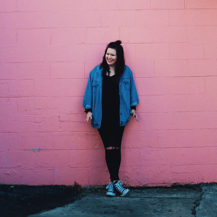 A woman in denim leans happily against a wall painted pink, smiling with her ankles crossed.