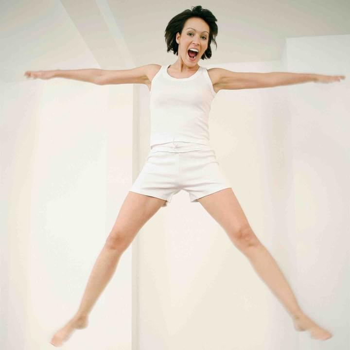A woman dressed in white jumps, looking free and happy.