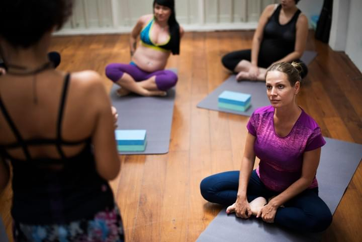 Women sit on you mats listening to the teacher at a pregnancy yoga class.