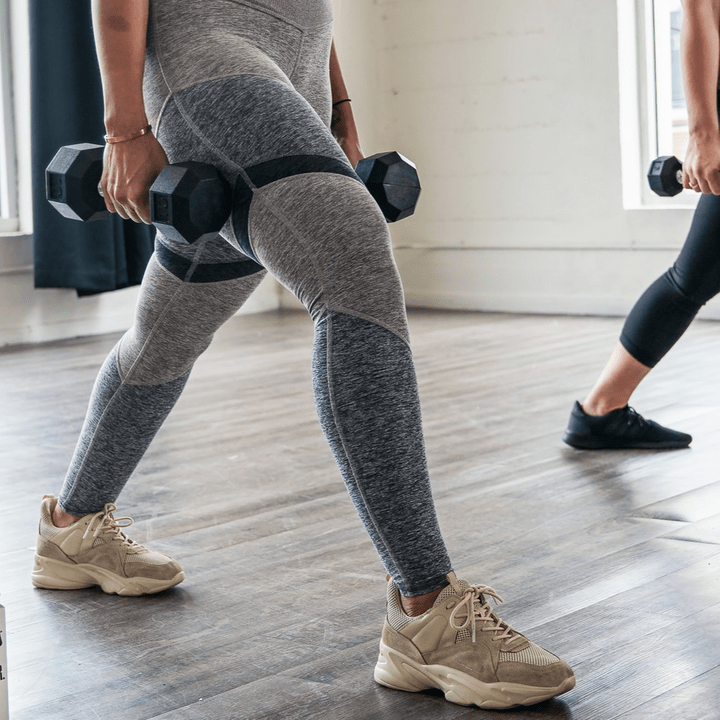 legs of person exercising with gray athletic pants and two dumbells one in each hand