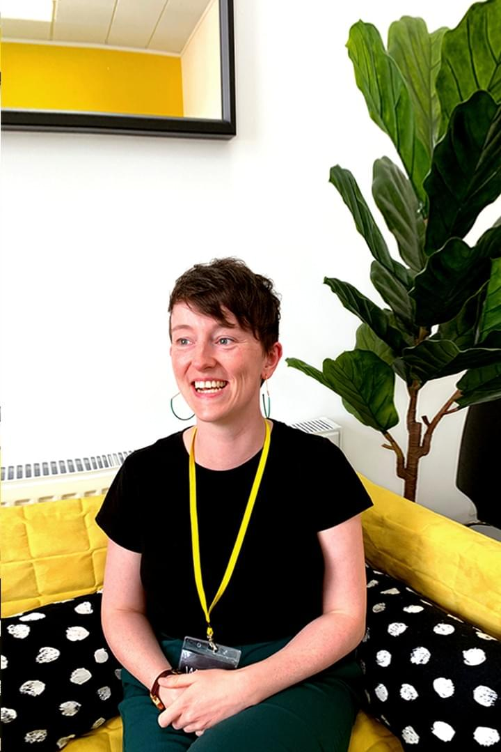 We Are Brass Tacks. Internal comms agency. Nebosh accredited. Senior Creative Lead sitting on yellow couch.