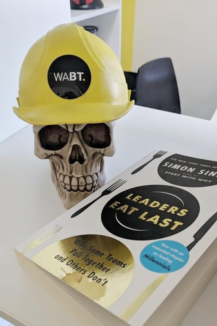 We Are Brass Tacks. Internal comms agency. Fred the Head. Skull with hard hat sitting beside book.