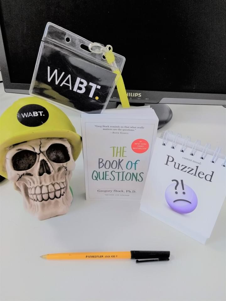 We Are Brass Tacks. Internal comms agency. Fred the Head. Book of the month. The Book of Questions. Skull with hard hat sitting beside white book yellow pen and puzzled emoji