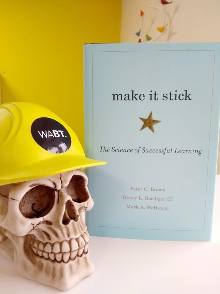 We Are Brass Tacks. Internal comms agency. Fred the Head. Book of the month. Make it Stick. Skull with hard hat sitting beside pale blue book.