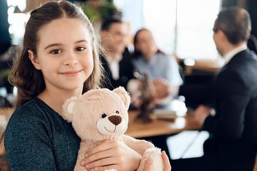 Girl holding teddy bear while parents talk to lawyer