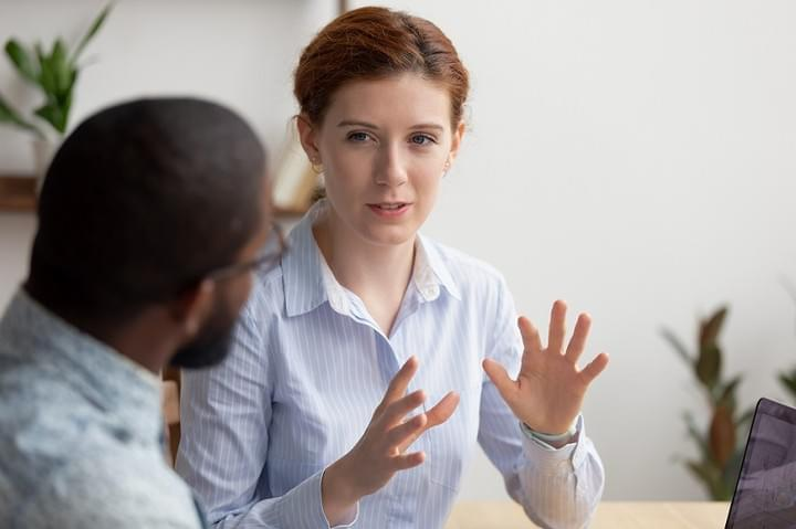 Female attorney gesturing with hands while explaining to client