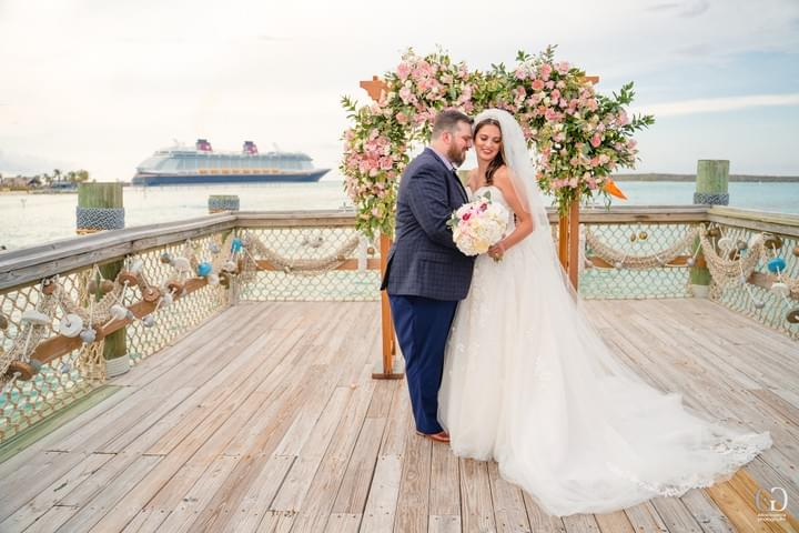 Photo of bride and groom on a dock in front of a floral altar.
