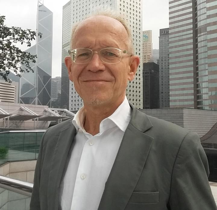Christian Masset taking a portrait in front of office buildings in Central