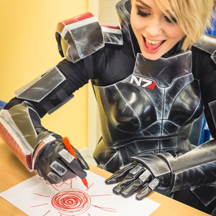 A happy cosplayer drawing a red sun. The character is Commander Shepherd from Mass Effect.