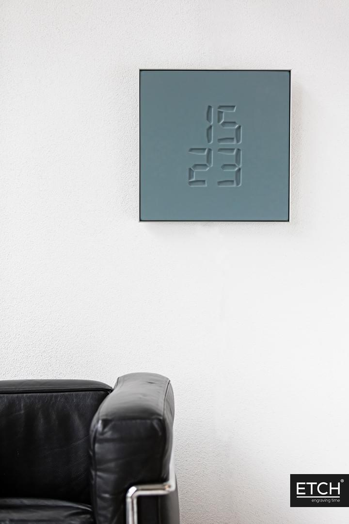 ETCH Clock hanging on wall