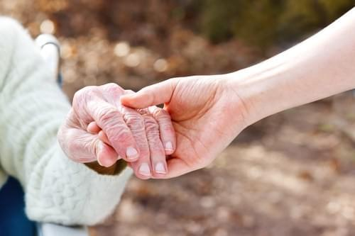 Older woman holding hand with care giver