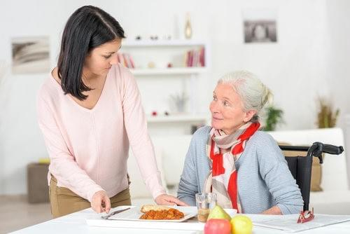 A Caregiver assisting her client with a food preparation.
