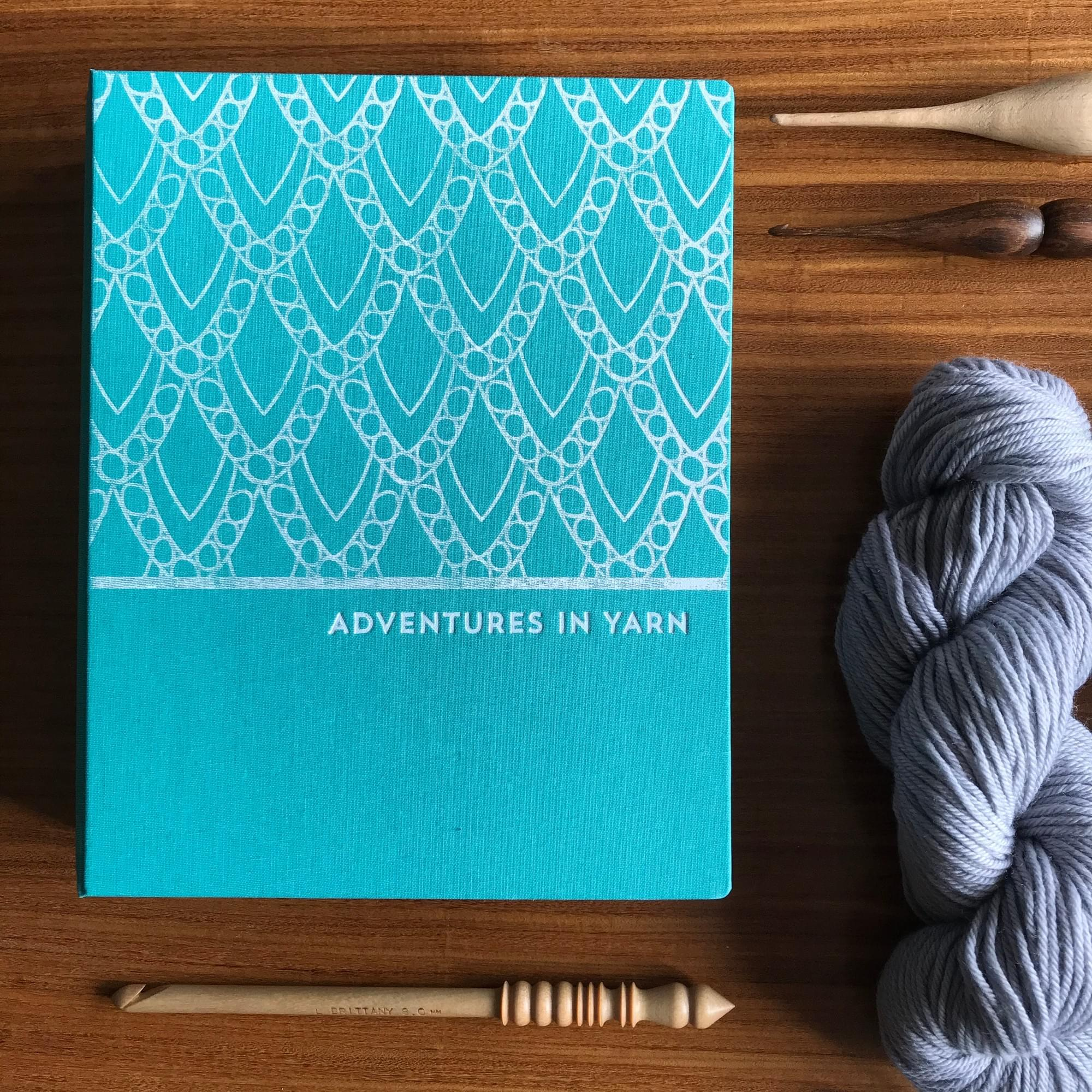 A beautiful blue cloth bound organiser with silver design lays on a table next to a skein of yarn and a crochet hook
