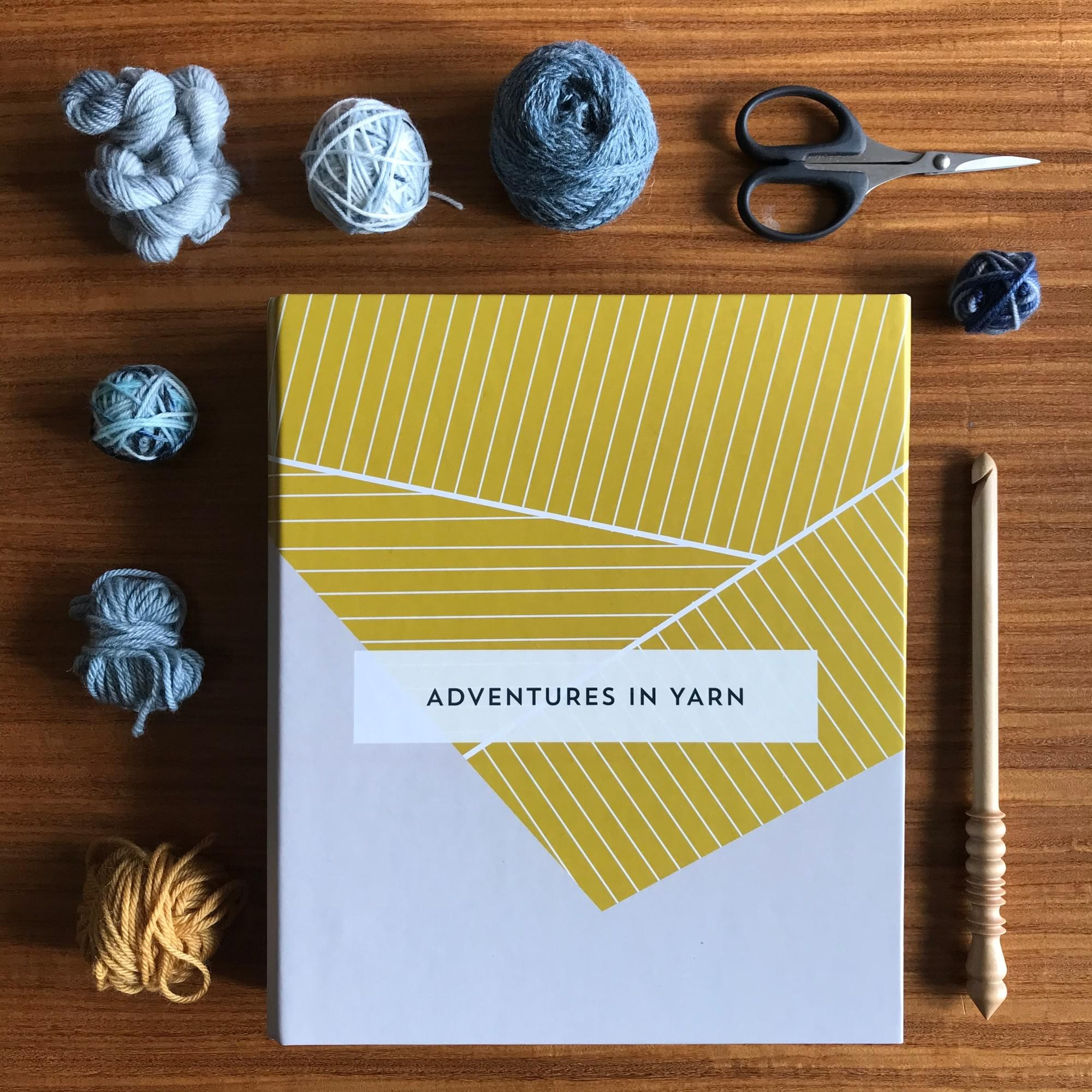 a beautiful hardback notebook organiser lays on a table. The book is coloured grey and mustard, with a folded paper design on the cover.