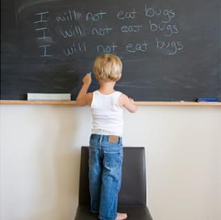Boy writes with his left hand on a chalk board.