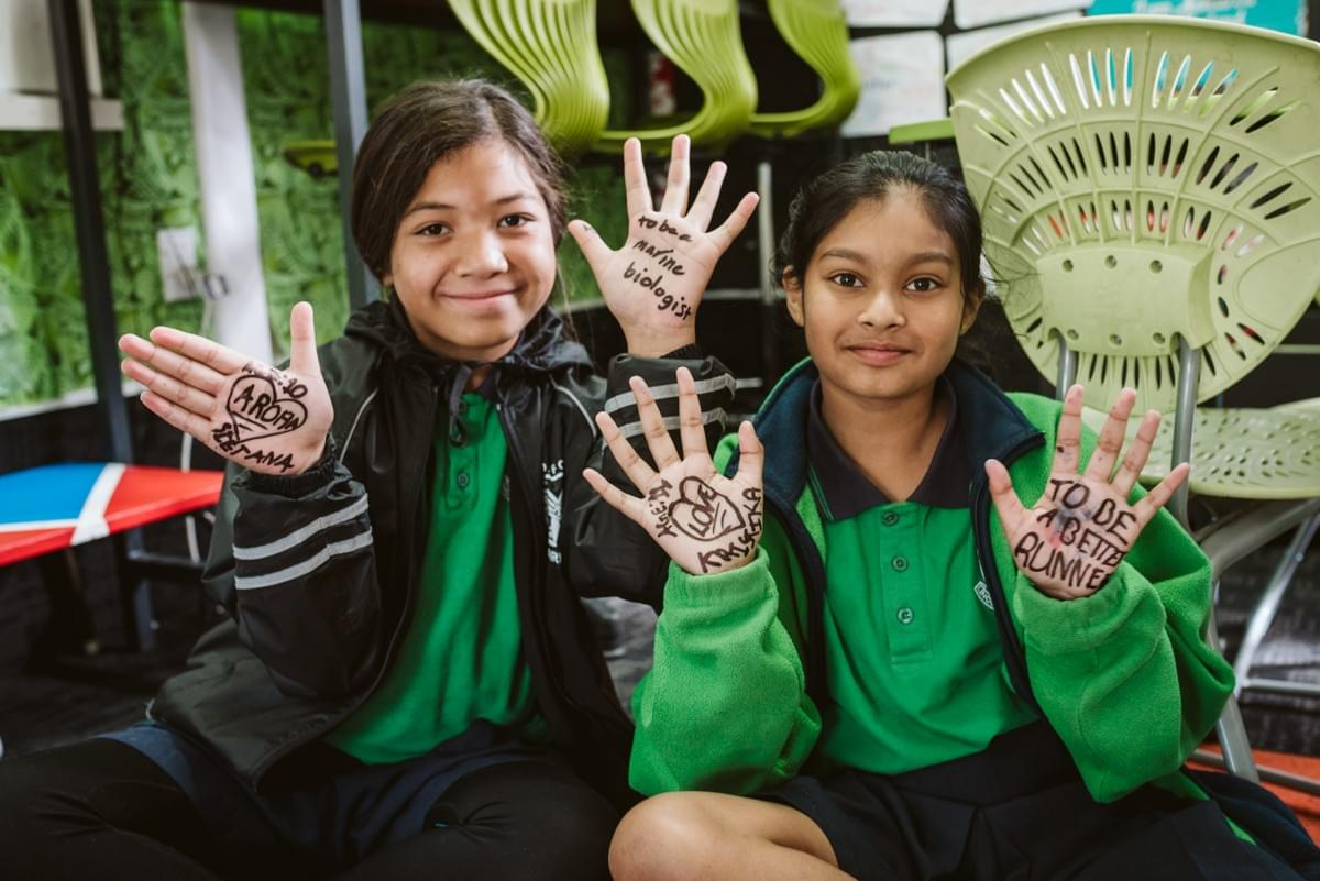 "Two young girls sitting on the classroom floor, holding their hands with writing on their palms toward the camera, that say ""to be a better runner"", ""to be a marine biologist"" and ""aroha""."