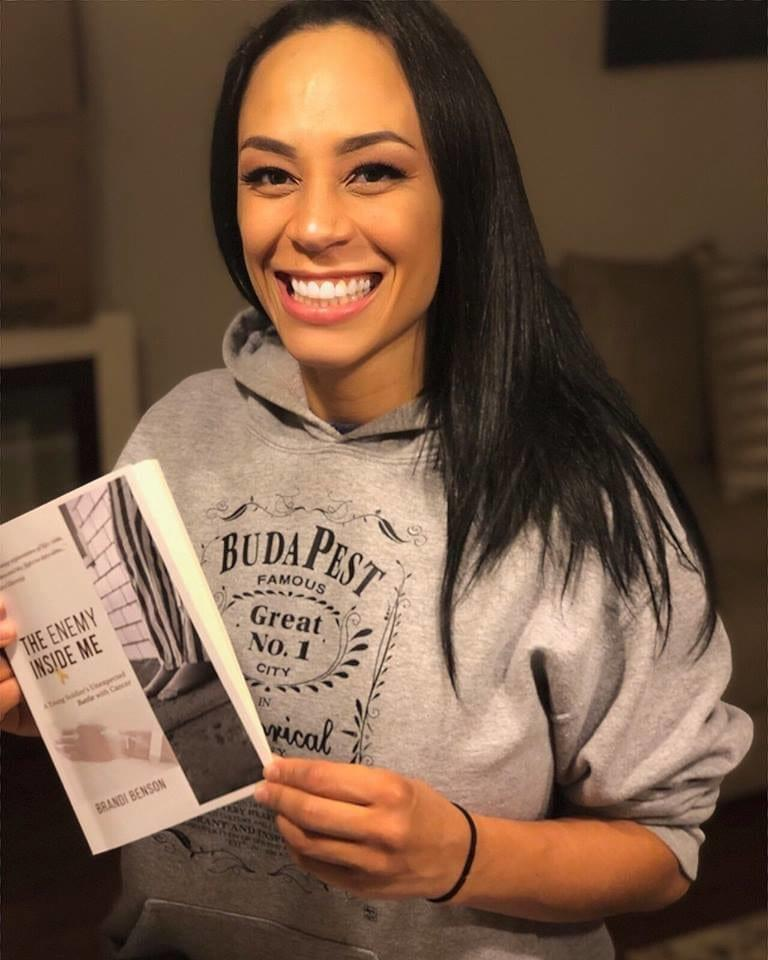 "Author, Brandi Benson holding a copy of her book - ""The Enemy Inside Me"""