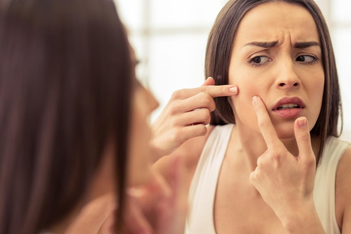 Upset Young Woman Looking in Mirror at Acne on Cheek